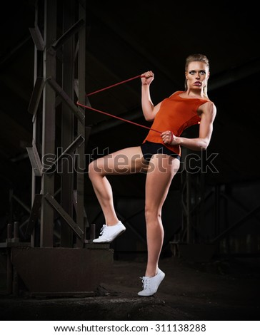 Young sporty woman in orange skirt (dark version) - stock photo