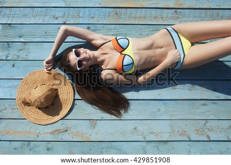 Young sporty woman in the bikini sunbathes on the beach on the blue wood background. - stock photo