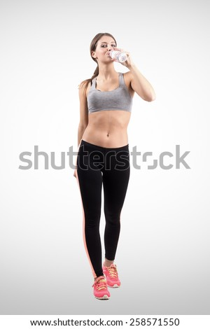 Young sporty woman jogger drinking water from the bottle. Front view. Full body length portrait over retro background with vignette. - stock photo