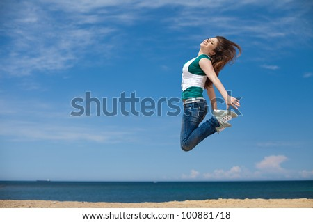 Young sporty woman jumping against the clear blue sky on the beach - stock photo