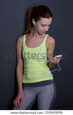 young sporty woman listening music with phone over grey background - stock photo