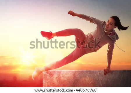 young sporty woman outdoors. the girl is engaged in parkour. - stock photo