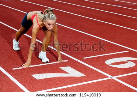Young sporty woman preparing to run at the start line - stock photo