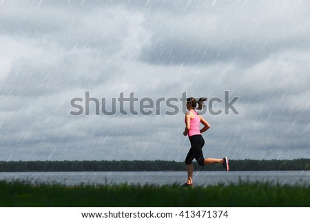 Young sporty woman running at rainy day - stock photo