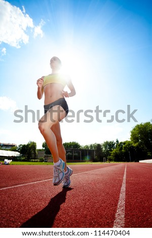 Young sporty woman running on sunny day - stock photo
