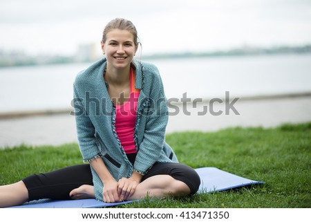 Young sporty woman sitting and relaxing at open air