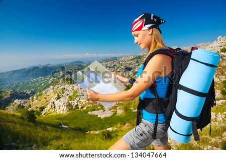 Young sporty woman standing on the peak on mountain watching on map, extreme adventure, happiness and freedom concept - stock photo