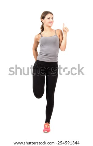 Young sporty woman stretching leg with thumbs up gesture.  Full body length portrait isolated over white background. - stock photo