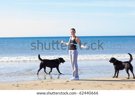 Young sporty woman surrounded by two dogs on the beach - stock photo