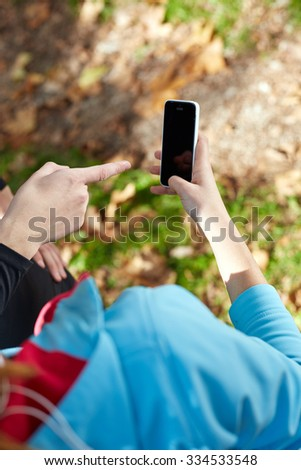 Young Sporty Woman Taking a Selfie at Park. She is Looking at Smart Phone - stock photo