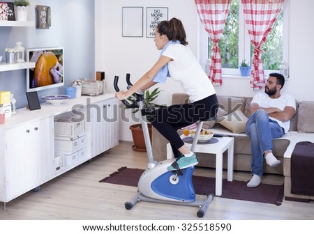Young sporty woman training on exercise bike in the living room while husband is Relaxing and watching tv, shallow depth of field  - stock photo
