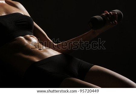 Young sporty woman training with the dumbbell