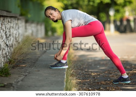 Young sporty woman tying running shoe laces in park in beautiful summer day. Workout in a Park. Sport fitness model caucasian ethnicity training outdoors. Fitness and healthy lifestyle.