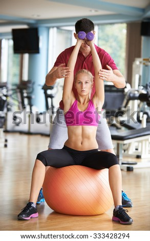 young sporty woman with trainer exercise weights lifting in fitness gym - stock photo