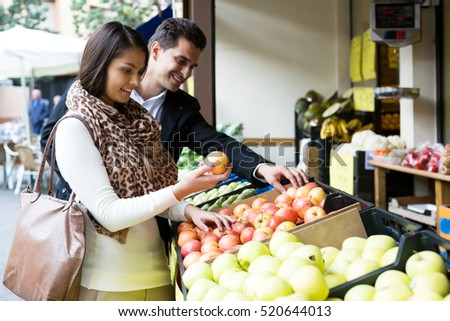 Young spouses choosing sweet fruits in grocery outdoors. Focus on the woman