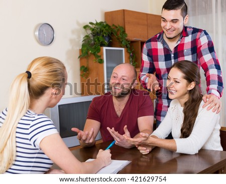 Young spouses sitting with documents and asking american friends for advice - stock photo