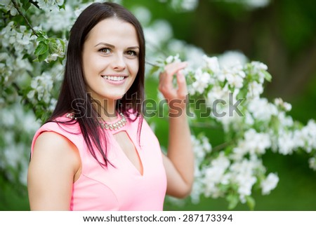 Young spring fashion woman. Trendy girl in the flowering trees in the spring summer garden. Springtime or summertime. Lady in spring landscape background. Allergic to pollen of flowers.Spring allergy - stock photo