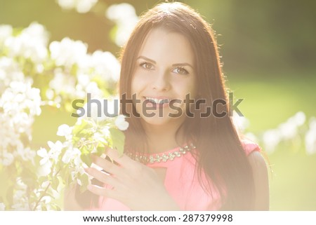 Young spring fashion woman. Trendy girl in the flowering trees in the spring summer garden. Springtime or summertime. Lady in spring landscape background. Allergic to pollen of flowers. Spring allergy - stock photo