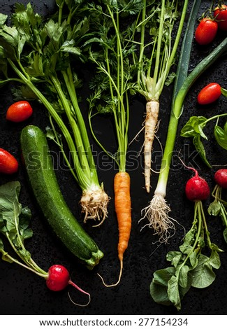 Young spring vegetables on black chalkboard from above. Carrots, tomatoes, zucchini, leek, radish, celeriac, parsley and basil - fresh harvest from the garden. - stock photo