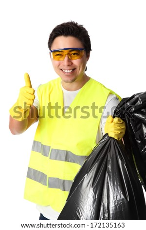 Young standing wearing a reflective vest, gloves and safety glasses. Holding a black garbage bag. White background.