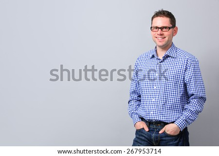 Young standing with hands in pockets and smiling on gray background - stock photo