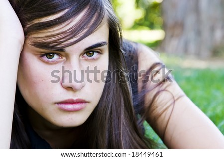 Young staring woman laying on the grass - stock photo