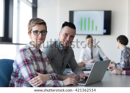 young startup  business people, couple working on laptop computer,  businesspeople group on meeting in background at office interior - stock photo