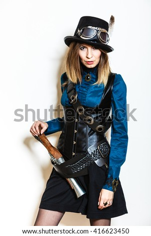 Young steampunk islolated girl on white wearing fancy hat. Fantasy old fashion with stylish topper goggle holding gun.