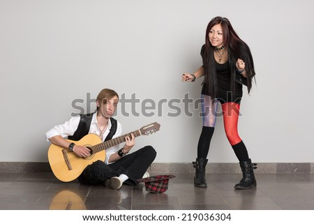 Young street musicians are musical number.Interracial young couple, Asian woman and Caucasian man. - stock photo