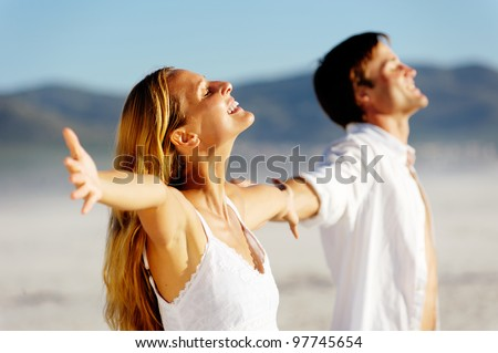 Young stress free couple enjoy the summer sun on the beach. Arms out, heads back and carefree attitudes.