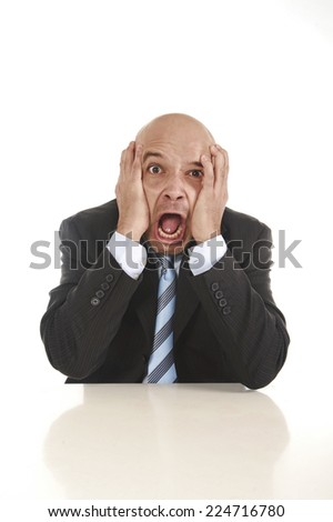 Young stressed businessman in suit and tie sitting on desk desperate crying and collapsed in financial crisis and work problems isolated on white background - stock photo