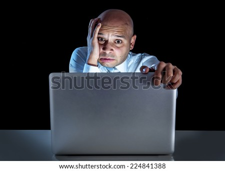 young stressed businessman working on computer laptop late at night in suit and tie isolated on black background looking frustrated watching on internet disaster work situation - stock photo