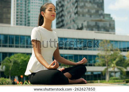 Young stressed hispanic business woman doing yoga outside office building, sitting in lotus position with hands on knees in the street. Concept of long working hours and need of stress free break - stock photo