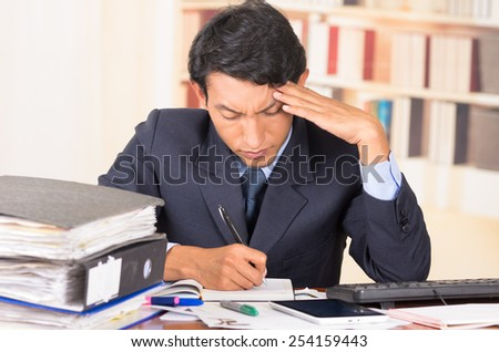 young stressed overwhelmed business man holding head with his hands looking at piles of folders on his desk
