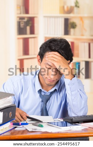 young stressed overwhelmed business man with piles of folders on his desk