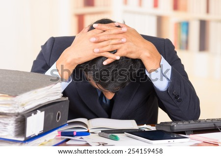 young stressed overwhelmed business man with piles of folders on his desk holding his head looking down - stock photo