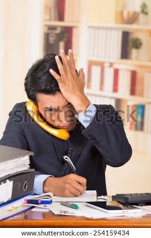 young stressed overwhelmed business man with piles of folders on his desk talking on the phone - stock photo