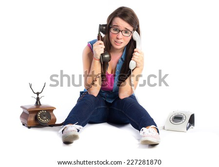 Young stressed woman holding two telephones isolated on white background  - stock photo