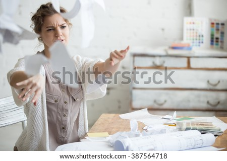 Young stressed woman sitting at desk in a little office or home mad at work, ripping documents with frustrated facial expression. Throwing around scraps of paper. Negative human emotions - stock photo