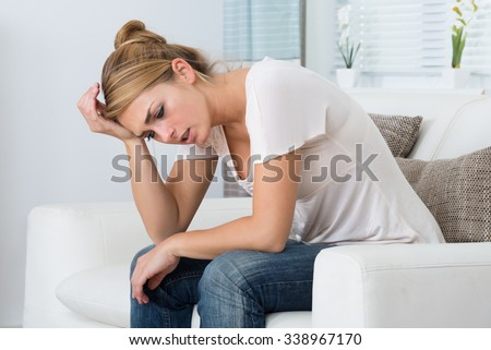 Young stressed woman sitting in living room at home - stock photo