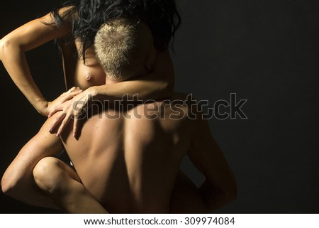 Young stripped pair of sexual woman in trainers sitting on man with strong muscular body standing with back on black studio background copyspace, horizontal picture - stock photo