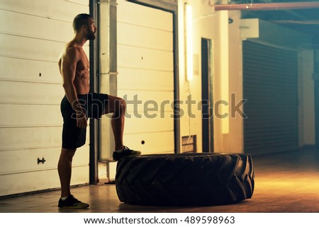 Young strong man is preparing for flipping out tire.