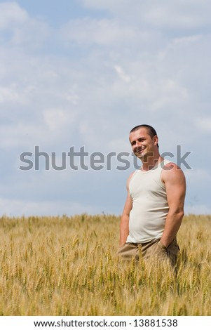 Young strong man with t-shirt in a wheat field