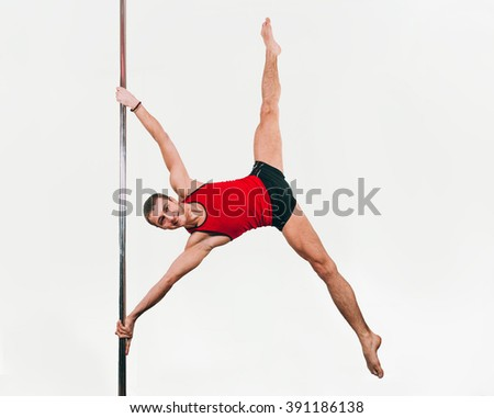 Young strong pole dance man doing iron x - stock photo
