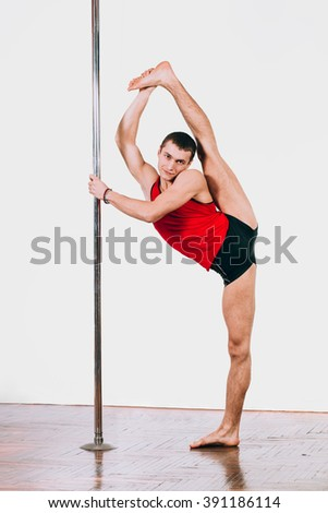 Young strong pole dance man on a twine near the pole - stock photo