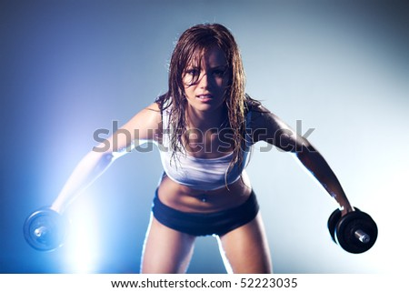 Young strong sexy woman with dumbbells. Focus on face. - stock photo