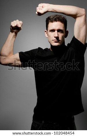 Young strong slim man in black t-shirt posing on gray background. - stock photo