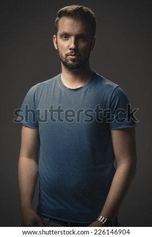 Young strong slim man in  t-shirt posing on gray background.  - stock photo
