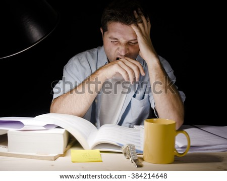 Young student at home desk reading and yawning tired at night with pile of books and coffee cup preparing exhausted an exam in university education concept - stock photo