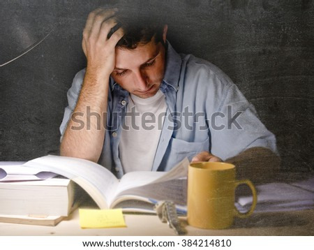 Young student at home desk reading studying at night with pile of books and coffee cup preparing exam in university education concept in dim light - stock photo